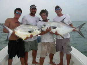 A happy group of clients on Tampa Permit fishing charter holding 2 large Permit.