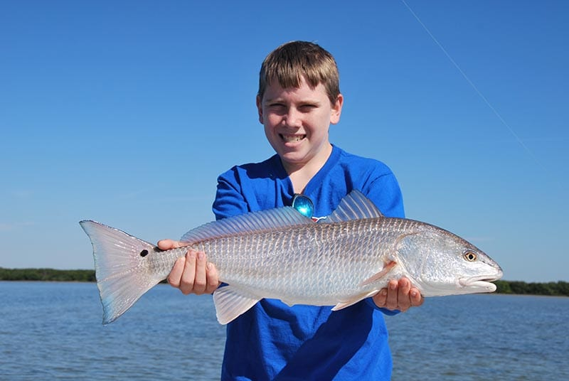 Tampa Bay fishing guide client olding large redfish during charter.